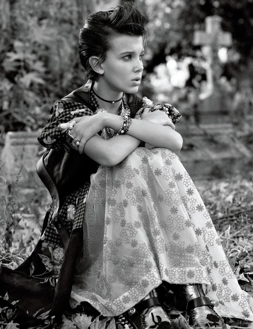 Fotografía de Millie Bobby Brown sentada en el bosque