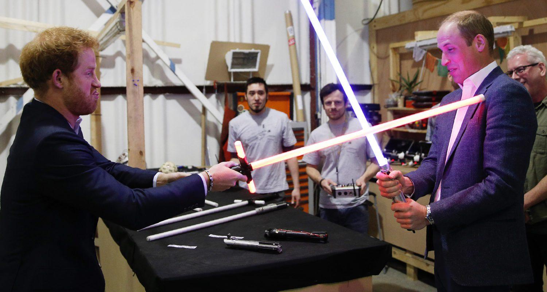 El príncipe William y el príncipe Harry luchan con los sables láser